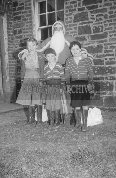 December 1957; A photo of Santa outside a school with a group of students.