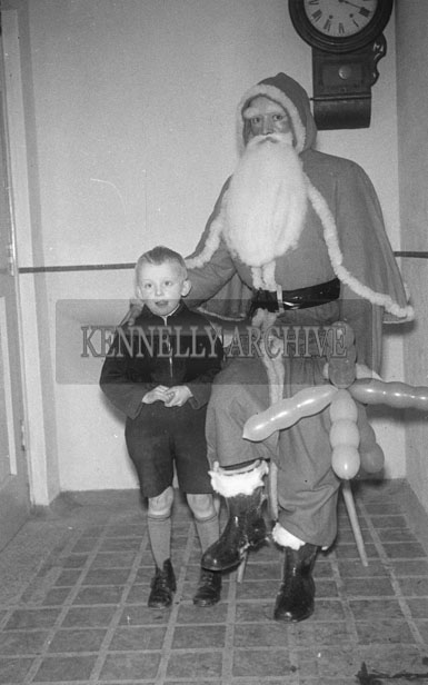 December 1957;  A photo of Santa inside a school with a student.