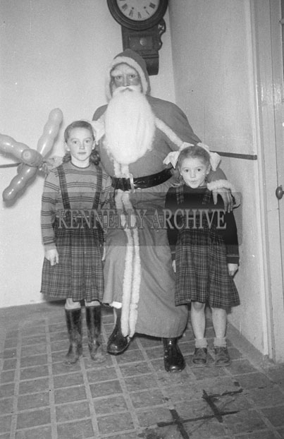 December 1957;  A photo of Santa inside a school with two students.