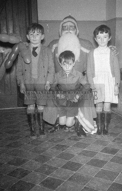 December 1957;  A photo of Santa inside a school with a group of students.