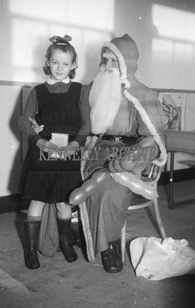 December 1957; A photo of Santa indoors with a student.