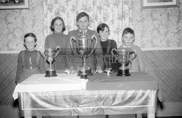 December 1957; A photo of children with Kerins O'Rahillys Trophies.