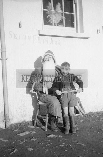 December 1957; A photo of Santa with a student on a visit to Castleisland National School.
