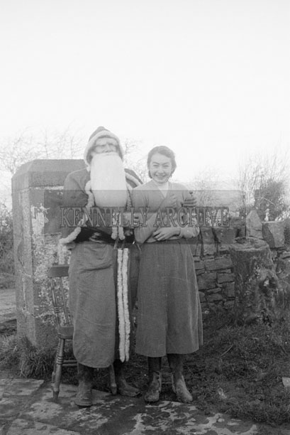 December 1957; A photo of Santa with a student on a visit to Knocknalougha National School.