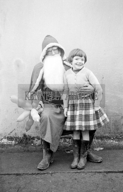 December 1957; A photo of Santa with a student on a visit to Lisselton National School.
