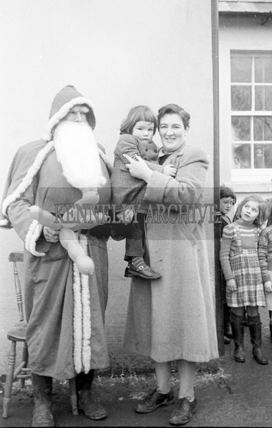 December 1957; A photo of Santa with a mother and child on a visit to Lisselton National School.