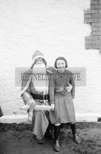 December 1957; A photo of Santa with a student on a visit to Coolard National School.