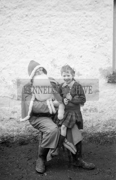 December 1957; A photo of Santa with a student on a visit to a National School.