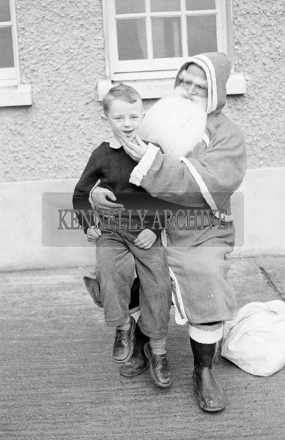 December 1957; A photo of Santa with a student in a convent school.