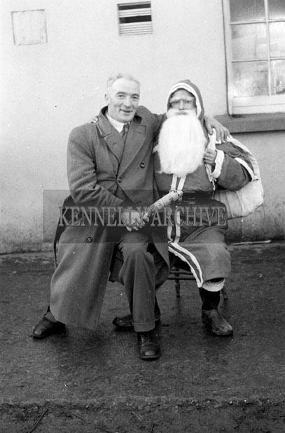 December 1957; A photo of Santa with a student at a National School.