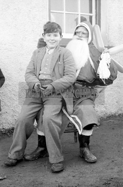 December 1957; A photo of Santa with a student at Toureenard National School.