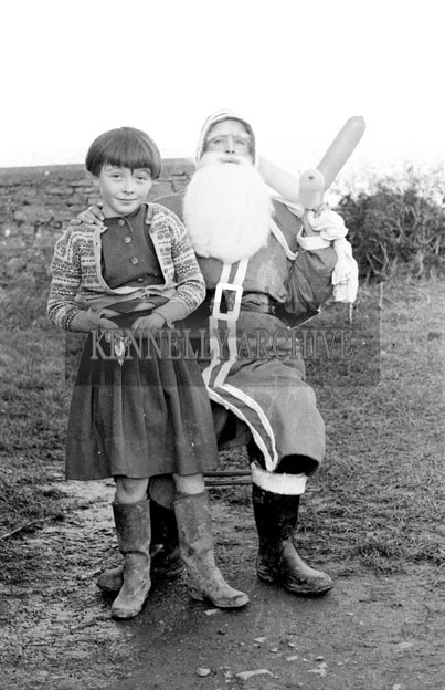 December 1957; A photo of Santa with a student outside a national school.