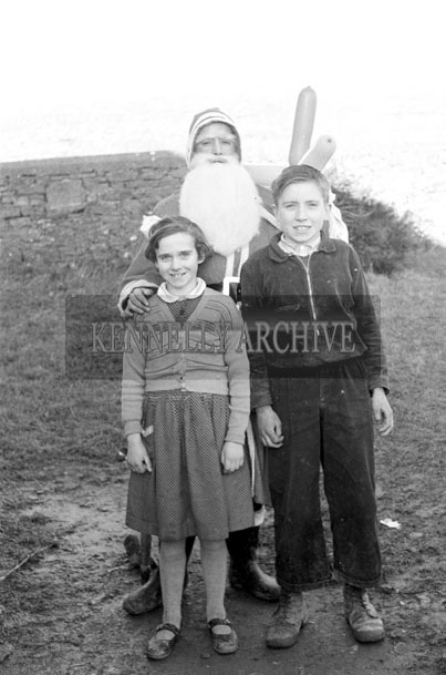 December 1957; A photo of Santa with students outside a national school.
