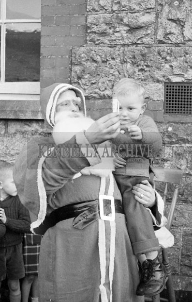 December 1957; A photo of Santa with a baby in a convent school in Castleisland.