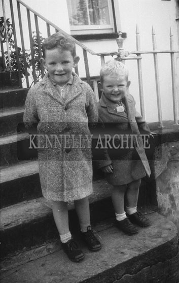 October 1962; Two boys pose for the camera in front of the Kennelly Home in Ashe Street, Tralee.