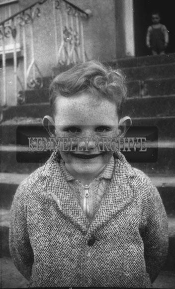 October 1962; A boy poses for the camera in front of the Kennelly Home in Ashe Street, Tralee.