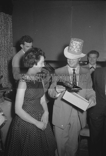 14th October 1962; A man showing a shoe to a woman at a dance which took place in Ballymacelligott.