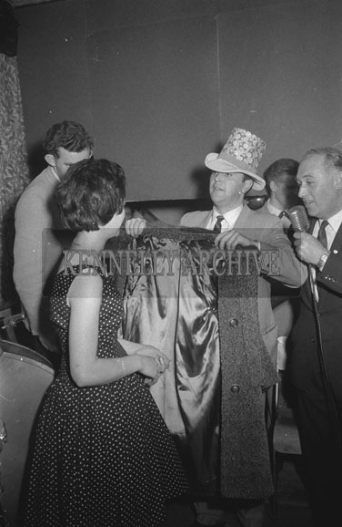 14th October 1962; A man showing a coat to a woman at a dance which took place in Ballymacelligott.