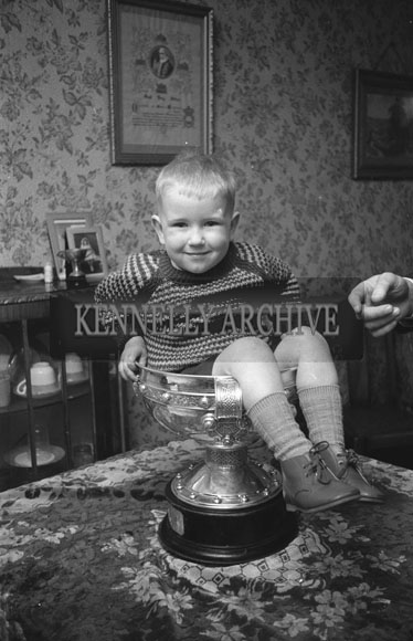 January 1962; A member of the Hennessy family sitting in the Sam Maguire Cup at home in Ballyduff.