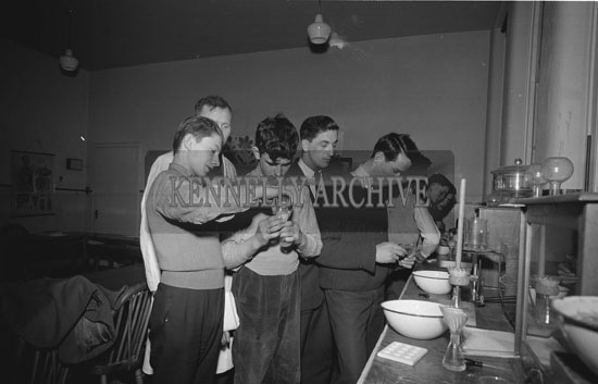 March 1962; Bobby Buckley (wearing a lab coat) and Rural Science students at Causeway Technical School carrying out a test on a consignment of fertilizer which was presented to them by the Albatross Fertilizer Company Ltd. The fertilizer was to be used as a plant food element on the experimental farm attached to the school.