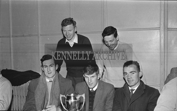 March 1962; A photo of a Basketball team with a trophy taken at the CYMS in Tralee.