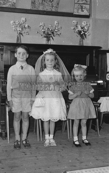 September 1962; A Communion photo of a girl taken with her siblings.