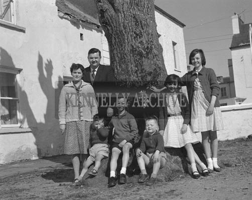 May 1964; A family poses for a photo outdoors.