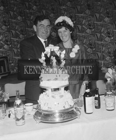 June 1964; A photo taken of a wedding couple cutting the cake at their reception held in the Hotel Manhattan.