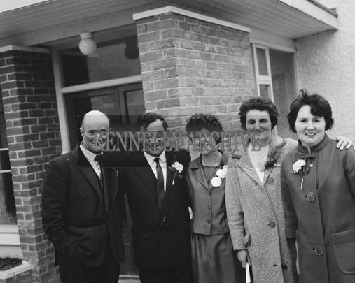 June 1964; A wedding party pose for a photo outside.