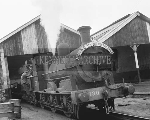 8th June 1964; A photo taken when over 150 members of the English and Irish Railway Record Societies travelled on a steam train from Limerick to Tralee via Listowel, to Fenit and then on to Killarney. The engine was a steam-driven 0-6-0 type, first brought into service in the 1860's. The line to Fenit was open in 1887 to transport fish catches.
