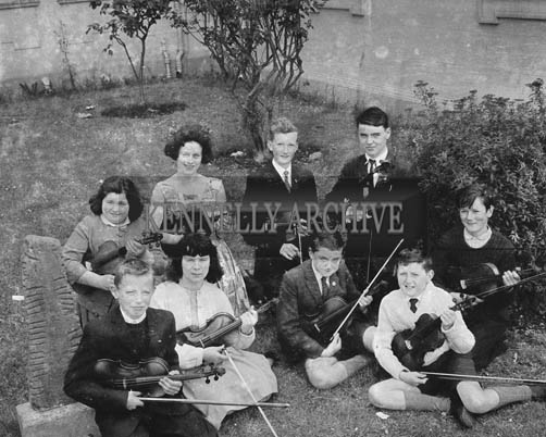 June 1964; Nine students from Micheal O'Duinn's music class in the Technical School in Tralee who passed the Royal Irish Academy of Music Examination. Front from left: Tom O'Brien, Mary Hogan, Diarmaid O'Foghludha and Padraig O'Foghludha. Back L to R: Ann Taylor, Joan O'Reilly, Sean P McCarthy, Joseph O'Shea and Patrick Stack.