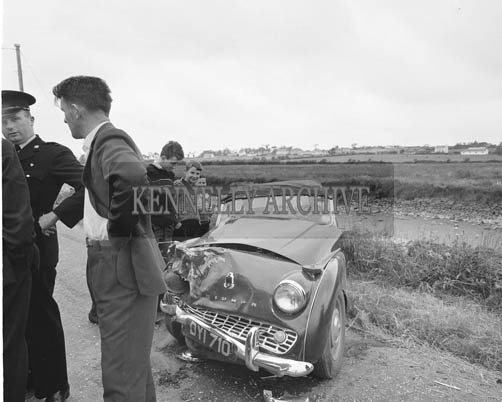 3rd July 1964; A photo taken at the scene of a car crash on the Tralee-Blennerville Road. Four people were taken to St Catherine's Hospital, Tralee. Two men, Mr Finbarr Murphy, Cork, and Mr Dermot Ashe, Dublin, were later discharged. Mr Murphy and Mr Ashe were travelling towards Tralee in one car at the time of the colision. In the other car, travelling towards Dingle, were 24 year old Garda Denis Moore, a native of Goulane, Castlegregory, and stationed in Athea, Co. Limerick, and Miss Josephine Enright of Athea. Garda Moore was detained at St Catherine's Hospital where he was stated to be in a critical condition. Miss Enright was also detained and her condition was described as fair. Both cars were extensively damaged.