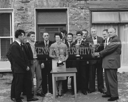 July 1964; The Committee of Dingle Festival with trophies presented by Messrs. Guinness for boat races at Dingle Regatta. L to R: Tony Sheehy, B. Grandfield (Vice-Chairman Regatta Committee),  John Sheehy, Mrs James O'Keeffe (Festival Secretary); Pat Sheehy, Frank Carroll (Joint Treasurer); Mr M. Begley, M.C.C. (Chairman Regatta Committee); Timothy J. Brosnan,  James Ashe (Guinness Agent), Michael Ashe (Guinness Agent), P. Begley, (Guinness Representative).