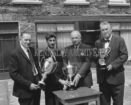 July 1964; The Committee of Dingle Festival with trophies presented by Messrs. Guinness for boat races at Dingle Regatta. Front L to R: Mrs James O'Keeffe (Festival Secretary); Messrs. B. Grandfield (Vice-Chairman Regatta Committee); Mr M. Begley, M.C.C. (Chairman Regatta Committee); P. Begley, (Guinness Representative); James Ashe, (Guinness Agent), T. Galvin (Chairman Festival Committee); Leo Brosnan, (Secretary). Back Row L to R: Messrs. John Brosnan (Joint Treasurer); Tony Sheehy, Frank Carroll (Joint Treasurer); John Sheehy, Pat Sheehy, Michael Ashe (Guinness Agent); Timothy J. Brosnan.