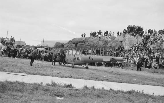 5th-12th July 1964; An Air Corps helicopter gives a rescue demonstration at Fenit Festival. Lieut. Carey 'rescues' Commdt. McMahon. The Helicopter can carry seven people or two stretcher cases. It can fly at 120 knots and came from Shannon in 35 minutes.