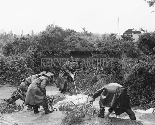 20th July 1964; Kerry County Council workers try to relieve the flooding in Kilflynn after a cloudburst in the area caused extensive water damage.