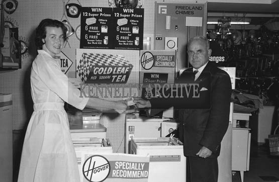 July 1964; A photo of Tralee UDC Chairman Jerry McMahon and Mary O'Shea, in Clifford's Shop in Tralee for the Gold Leaf Tea Free Draw.