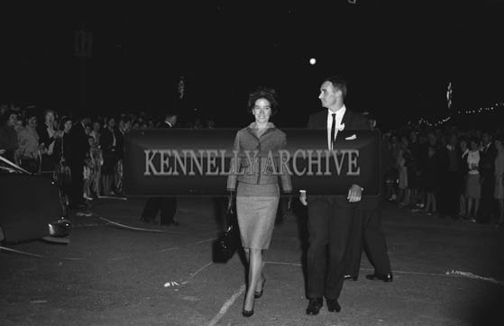 29th August-3rd September 1964; Mr Brian Sheehy escorting a Rose to the stage in Denny Street at the opening of the Festival of Kerry.