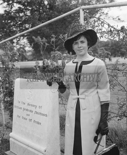 29th August-3rd September 1964; A Rose Contestant poses for the camera with the Rose of Tralee Monument in Tralee Town Park.