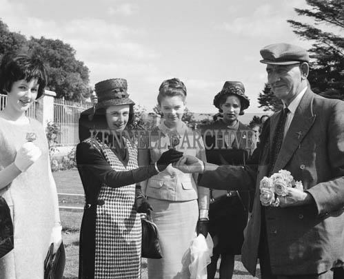 29th August-3rd September 1964; A man presents a Rose Contestant with a rose in Tralee Town Park.
