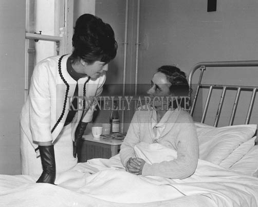 29th August-3rd September 1964; Rose of Tralee Margaret O'Keeffe speaks with a patient at the County Hospital, Killarney, during the Rose Tour.