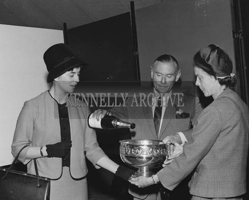 2nd September 1964; Rose of Tralee Margaret O'Keeffe presents the Carling Rose Bowl to Mrs King-Harmon, owner of 'Bonne', the winner the Carling Black Label Stakes at Ballybeggan Park, Tralee. Richard Beamish fills the Bowl with Champagne.