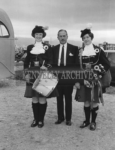 2nd September 1964; A man poses for a photo with two members of The London Girl's Pipe Band at Tralee Races in Ballybeggan.