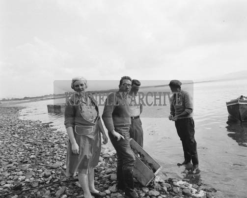 1st October 1964; A group of people in Fenit with the first oysters of the season.