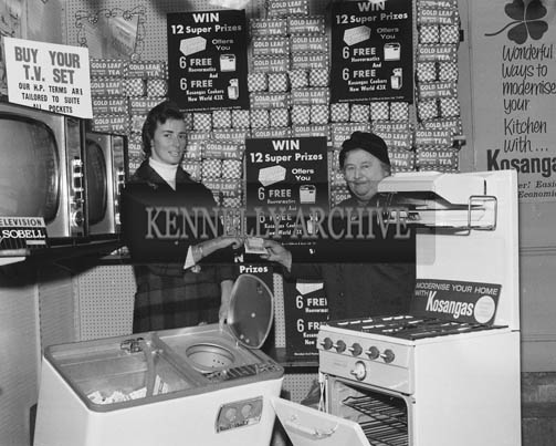 17th October 1964; Mrs Tom Clifford (left) draws the lucky coupon in the Free Gold Leaf Tea draw at Household Sales in Tralee for Mrs Jack Brosnan, Ballymacelligott.