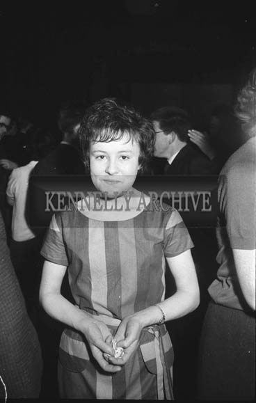 15th January 1964; A young woman smiles for the camera at a dance in the CYMS in Tralee. Music at the dance was provided by the Royal Showband.