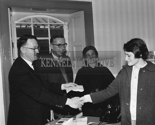 November 1964; Mr P. Hennigan, Station Master, Tralee, presents the prizes to the winners of the CIE Essay Competition.