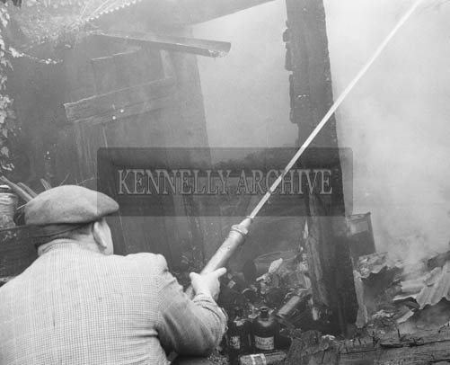 March 1964; A photo of a member of the fire brigade fighting a fire in Kerry.