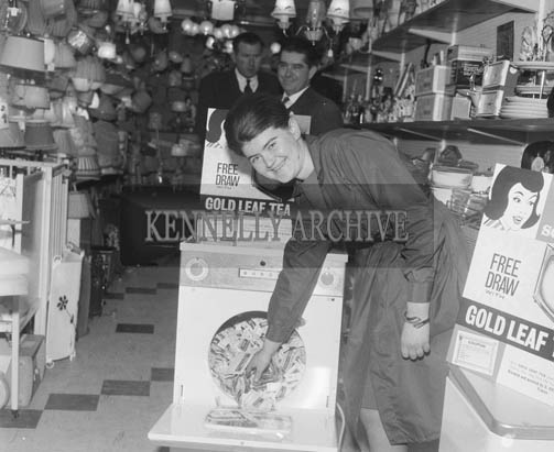March 1964; Miss L. Flynn of household goods, drawing for the final two 19 Television Sets in the Gold Leaf Tea Free Draw in Clifford's Shop, Tralee.