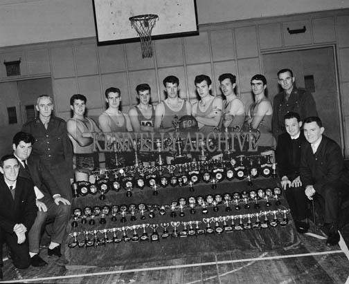 December 1964; The FCA Basketball Team and officials with some of the trophies won by the team. In 1964 they own the International LOTA Tournament in Cork, the Munster Open Blitz Championship, the Brass Rail Tournament and the All-Army Championship. From left: CQMS T. Comerford, R. O'Donnell, Lieutenant M. Brassill, F. Fitzgibbon, S. Burrows, J. Kissane, C. Spring, B. Burrows, E. Stack, D. O'Shea, Commandant M. Scannall, Sargeant M. Murphy.